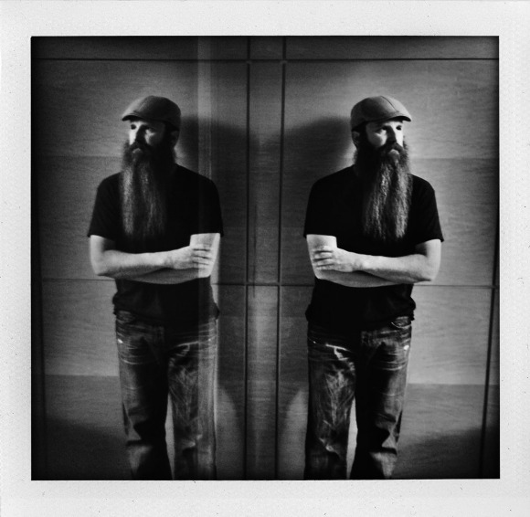 """It's not everyday that a girl walks into a Chicken Wings joint and encounters one of the most impressive beards she's ever seen; but when you're a lady of Beards of Denver, sometimes that hankering for chicken wings and an affinity for discovering great beards collide, and great things happen. Beards of Denver, meet Sam. Originally from Saginaw, Michigan, he's lived in Denver for 14 years, and his amazing beard is a testament to his scholarship; he's been growing his beard for three and a half years, the length of his stint as a doctoral student in the creative writing program at UC Denver. Sam loves having his beard, and stated its's his """"friend maker"""" and helps him get his message across and presents a certain constitution, one of patience and that he works on things. He loves the subliminals that come from the noverbals of the beard, and I don't think we could've stated it an better than that. Sam's wonderful wife Pari loves his beard, and has actually only seen him once without it. She says it's also softer than day-old scruff and encouraged him to use morrocan oil in it. Sam is a huge fan of Al at Al's Barber Shop downtown on Larimer; Al makes sure Sam's beard is all trimmed up, particularly around his mouth, which we've learned is essential. Both Sam and Pari stated that Sam's beard changes interactions with people because he gets approached far more often with it than without. They say people build bridges?  Well, I think we have the proof here that beards do."""